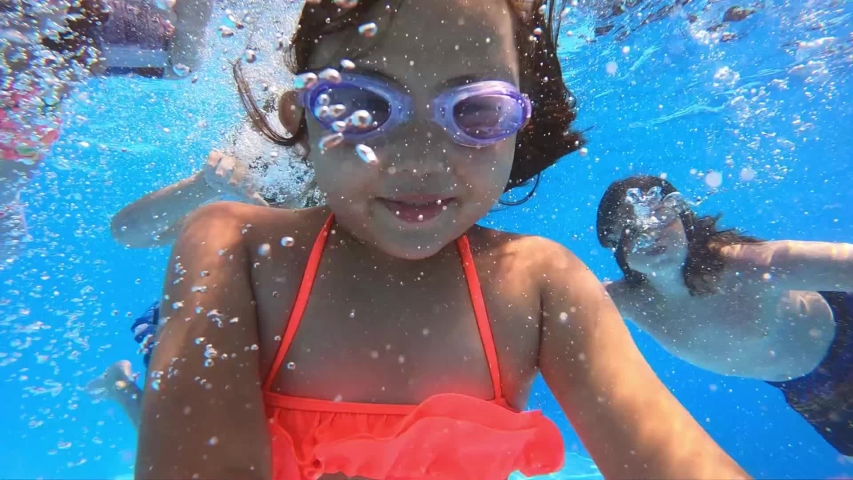 Underwater view of having fun group of children jumping and diving into swimming pool at pool party in summer sunny day. Happy children. Slow motion. Childhood, friendship, vacation concept