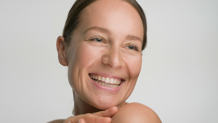 Close-up beauty portrait of young woman with smooth healthy skin, she gently touches her shoulders with her fingers on white background and smiles | Shutterstock HD Video #1041403423