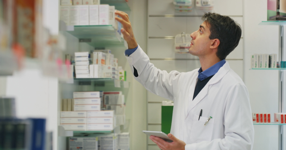 An young male pharmacist consultant is checking with a tablet medicines on the shelf of drug store.