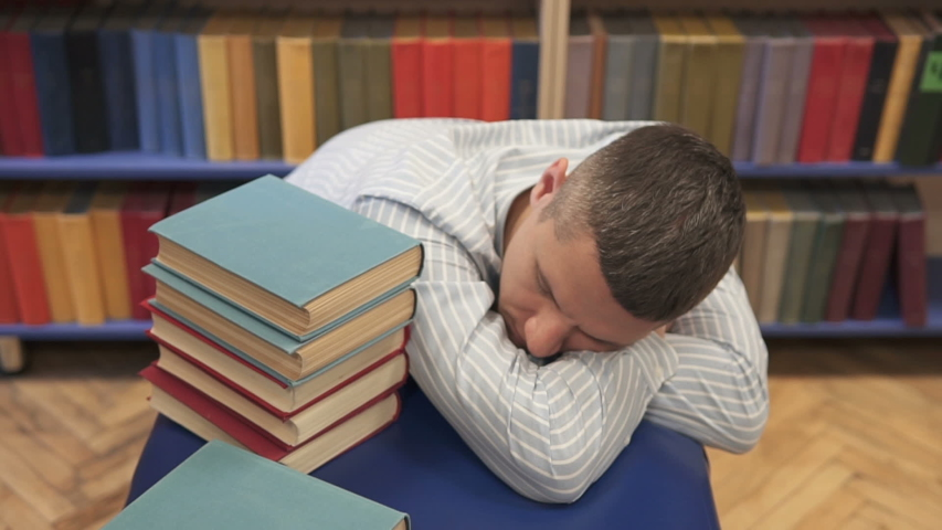Young man sleeping in the library | Shutterstock HD Video #1041405634