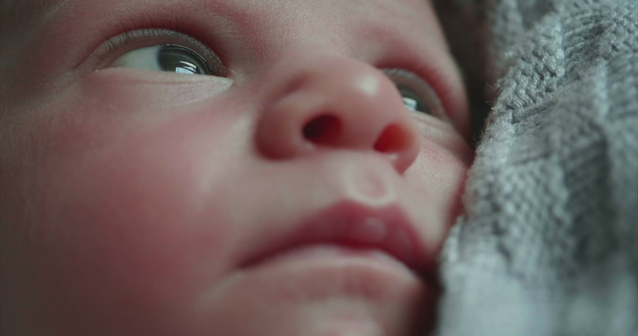 Authentic macro shot of a cute newborn baby is looking around and in the camera.Concept of children,baby, parenthood, childhood, life