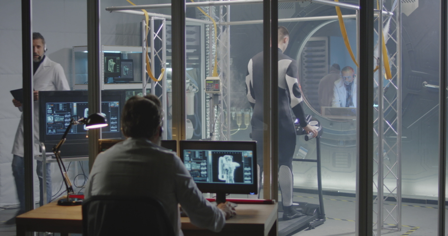 Medium shot of a male astronaut walking on a treadmill during a pre-flight test while scientists watching him #1041409069