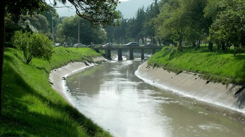 """Bridge and waterway """"humedal"""" green peaceful area in the city of Bogota, Colombia, wide shot"""