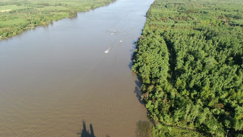 View from a drone of a wide river with leafy groves on the coast and boats sailing. Paraná River, Escobar, Argentina. | Shutterstock HD Video #1041434347