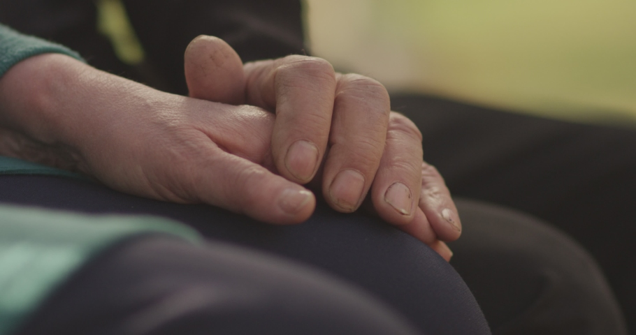 4K Faithful old couple holding hands. Close-up of hands of lovely aged couple caring and loving each other. Support trust in marriage relationship. Beautiful footage. Health care concept. Slow Motion.