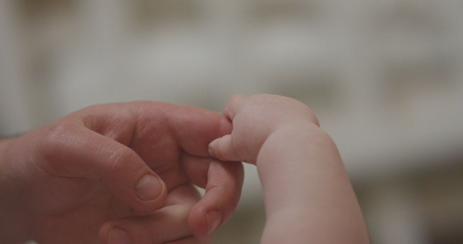 4K Closeup shot of baby's little cute hand reaching for father's loving finger . Baby holding parent's finger. Parent holding newborns hand in Slow Motion. Hand in hand. Father and newborn baby .  | Shutterstock HD Video #1041448492