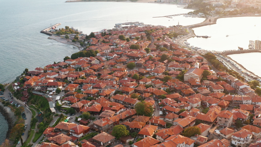 Lot red tiled roofs of houses aerial view from drone flying turn forward to old resort town of Nessebar, Bulgaria on peninsula in sea sunset day, summer. Tourism. Travel. Top view