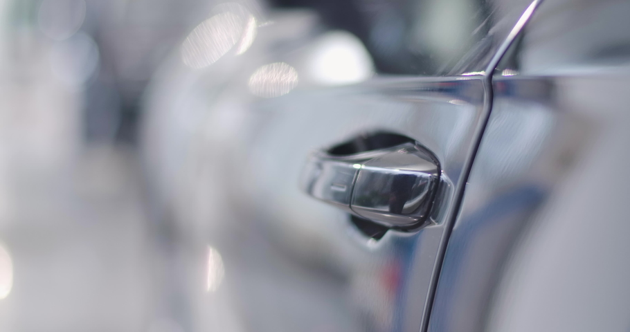Close-up of black car door handle opened by male Caucasian hand, man sitting into the salon and closing door. Car dealership, car business. Cinema 4k footage ProRes HQ.