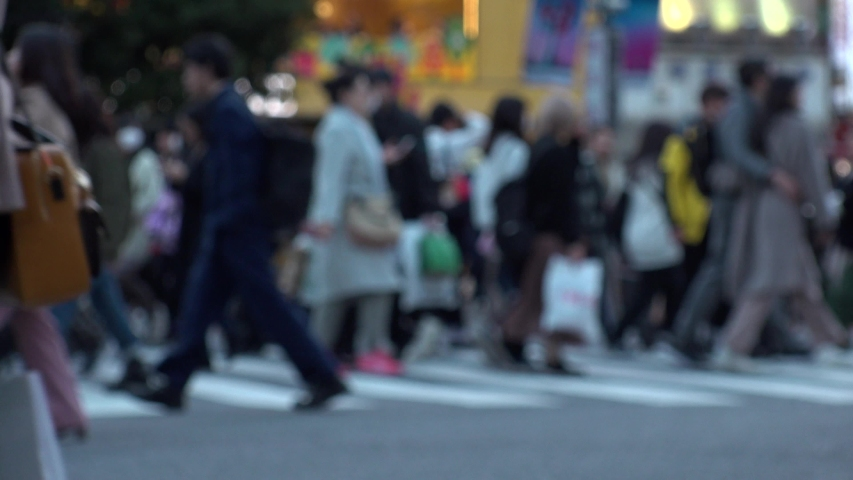 SHIBUYA, TOKYO, JAPAN - NOVEMBER 2019 : Crowd of people at Shibuya Scramble Crossing in busy early evening rush hour. Many commuters and tourists at the street. Shot in sunset time. In front focus. | Shutterstock HD Video #1041460087