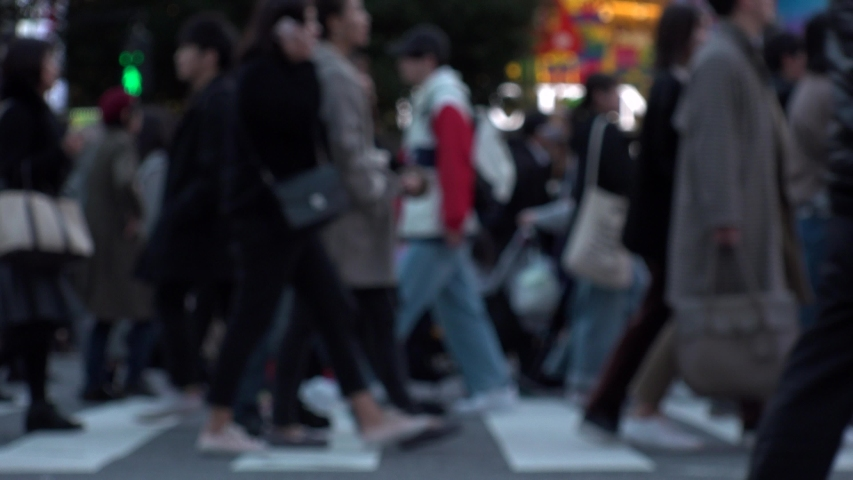 SHIBUYA, TOKYO, JAPAN - NOVEMBER 2019 : Crowd of people at Shibuya Scramble Crossing in busy early evening rush hour. Many commuters and tourists at the street. Shot in sunset time. In front focus. #1041460102