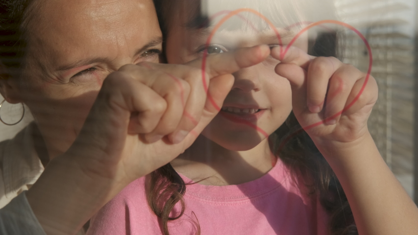 The love of mother and kid. Heart on the window. Mother with daughter hands drawn heart on a glass.