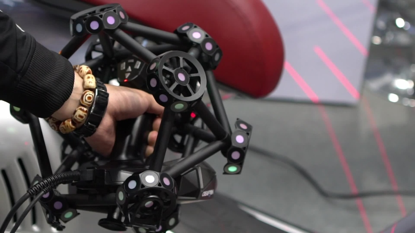 Taiwan-26 April, 2019: Man hand scanning a motorcycle using a measuring machine 3D scan high precision part for reverse engineering. Portable 3D scanning and probing system-Dan #1041475378