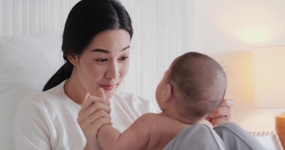 Close up mother and baby playing together on bed with happy emotion. Mother take care her baby with attractive smile. | Shutterstock HD Video #1041481237