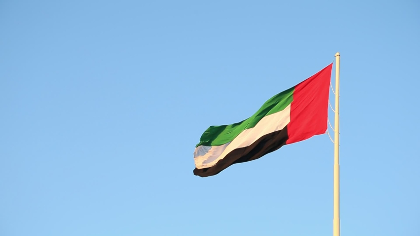 UAE flag waving in the sky, national symbol of UAE. UAE National Day. UAE flag day.