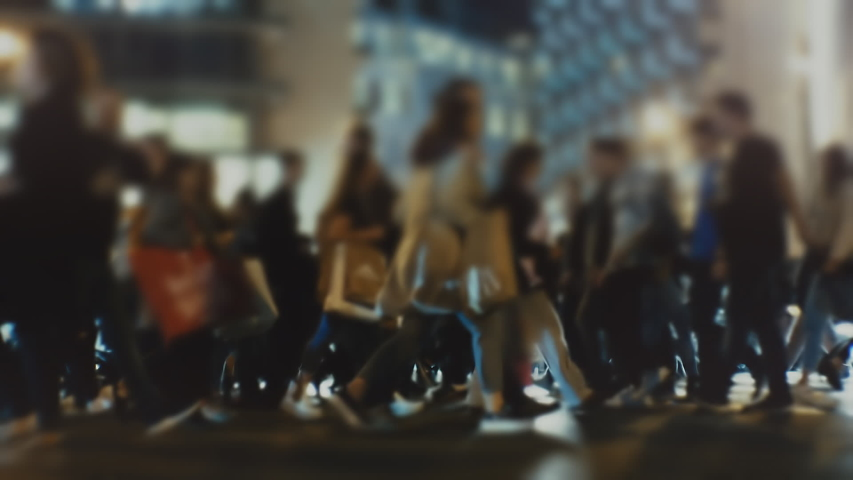 Shoppers and pedestrians on the street carry shopping handbags and cross the busy city intersection at night during the Black Friday week. Blurred | Shutterstock HD Video #1041495805