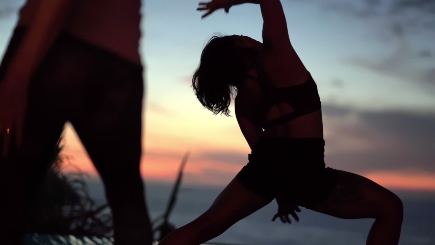 Yoga instructor transitions from warrior 2 to triangle pose in front of beautiful sunset in the distance