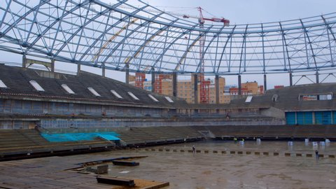 High-altitude cranes, metal girders of the roof, concrete tribunes and builders - this is the construction of a new stadium