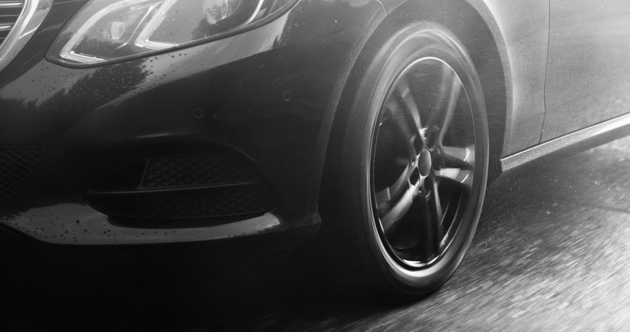 Reflecting everything around with its glossy surface, the premium car rides asphalt road where you can observe the suspension and how the tires perceive driving conditions. Black and white color  | Shutterstock HD Video #1041535441