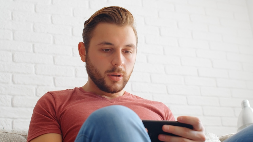Sports Fan Reaction Concept - Disappointed sports fan watching his favourite team/player on smartphone at home, 4k slow motion | Shutterstock HD Video #1041538063