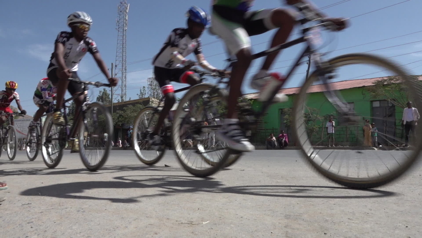 MEKELE, ETHIOPIA – MARCH 2019: Low angle slow motion of speed bicycle riders during local competition near Mekele, sports in Ethiopia