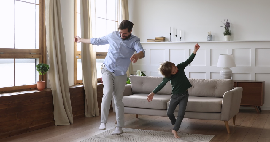 Playful crazy young daddy and cute kid son having fun dancing together in living room interior, happy funny active child boy copy father jumping laughing at home, carefree male family leisure indoors