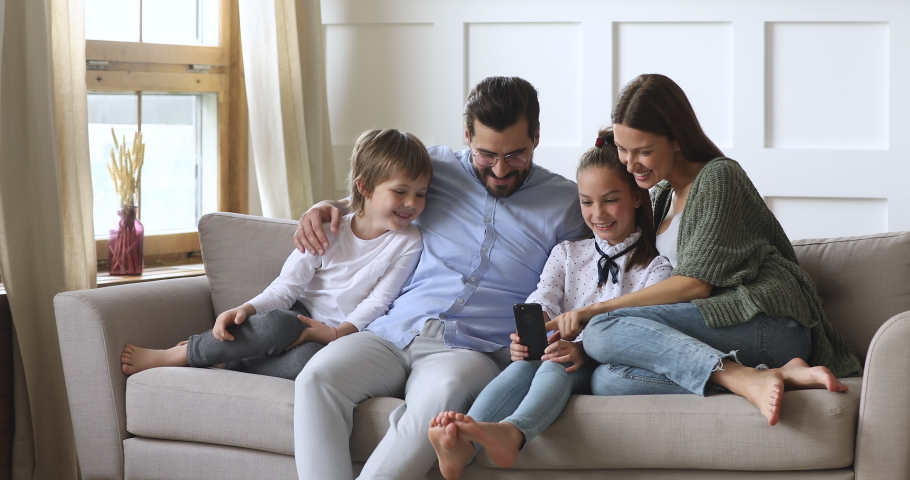 Happy family adult parents with cute school kids children relax on sofa using funny smartphone apps laughing having fun with technology together looking at phone screen take selfie play game at home Royalty-Free Stock Footage #1041538702
