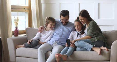 Happy family adult parents with cute school kids children relax on sofa using funny smartphone apps laughing having fun with technology together looking at phone screen take selfie play game at home