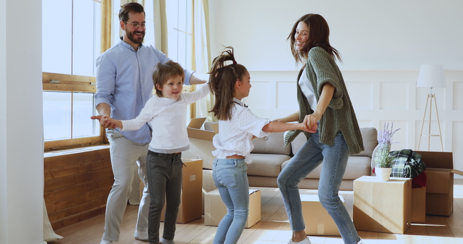 Happy family of four dancing jumping celebrating moving day removal in new home, young adult parents mum dad having fun with little cute kids children packing unpacking boxes after relocation concept Royalty-Free Stock Footage #1041538711