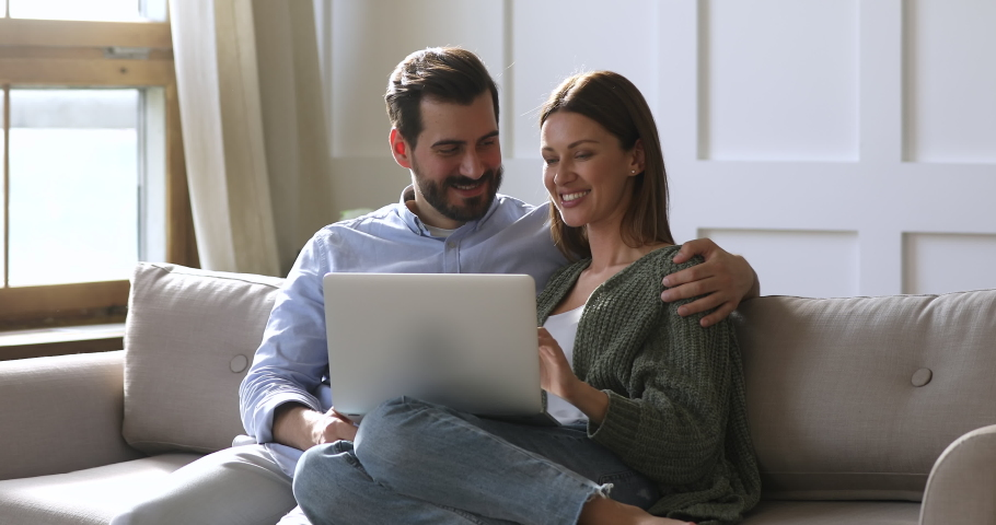 Happy husband and wife relaxing sitting on sofa enjoying using laptop computer, 30s young couple looking at notebook screen browsing internet choosing shopping online resting together in apartment