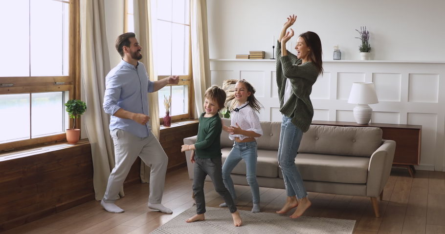 Crazy happy family young adult parents mum dad and cute funny active little children kids listening music dancing jumping together having fun in modern living room enjoying leisure lifestyle at home