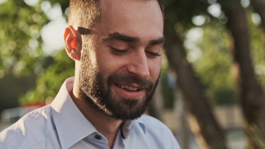 Close up view of Happy bearded businessman answering the call and talking by smartphone while sitting in park outdoors   Shutterstock HD Video #1041540667