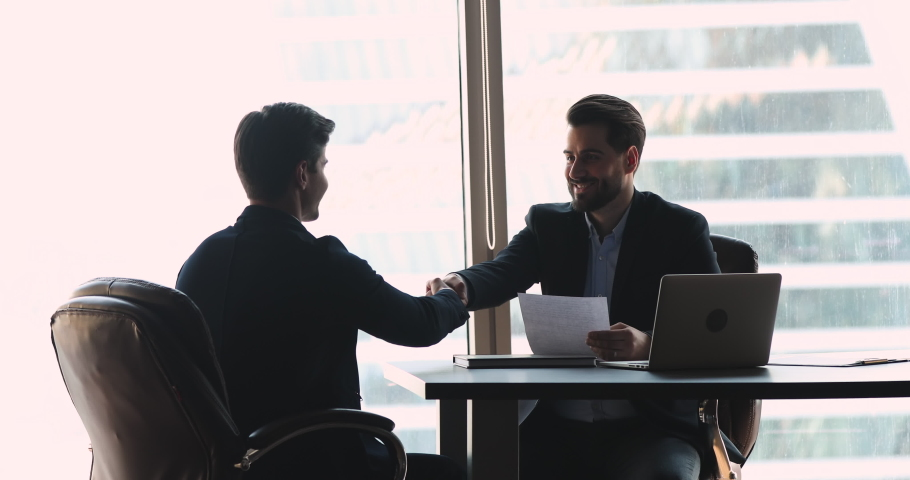 Confident businessman company employer wear suit handshake hire male vacancy candidate employee offering professional contract at job interview sit at modern office table, hr staff employment concept