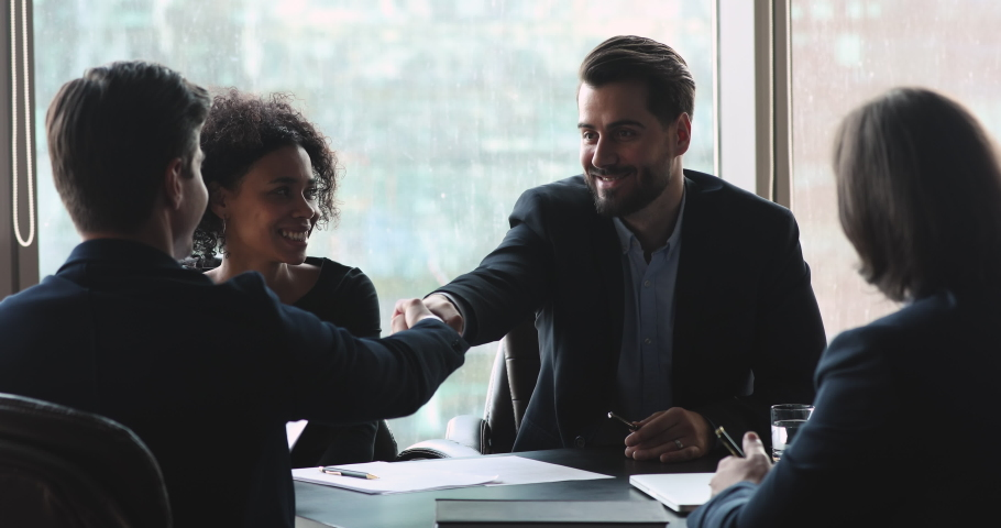 Smiling male executive wear suit make business agreement handshake businessman partner express respect and gratitude after successful team negotiations at international corporate group meeting Royalty-Free Stock Footage #1041547675