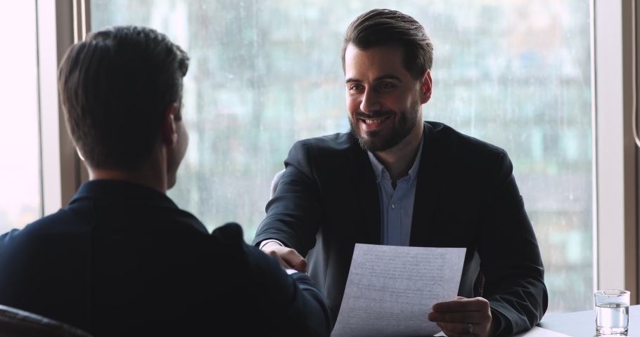 Confident businessman make agreement handshake business partner at meeting, male manager offering partnership contract to client customer, employer shake hand hire candidate at job interview concept Royalty-Free Stock Footage #1041547687