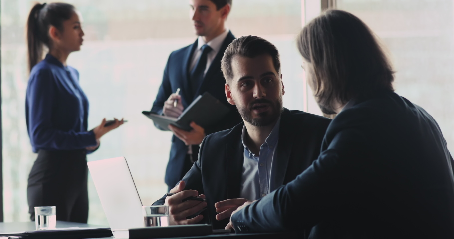 Serious businessman wear suit speaking to male colleague partner investor explaining strategy plan with laptop sit at meeting table, two professional businessmen talking in modern corporate office