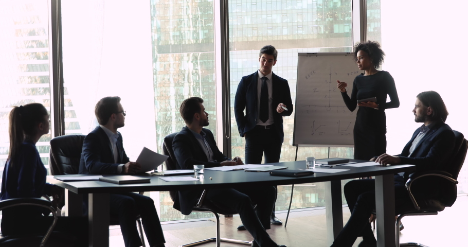 Training business leaders or sales managers wear suits communicate with executive clients audience teach staff group at workshop seminar giving flip chart presentation corporate discussion in office