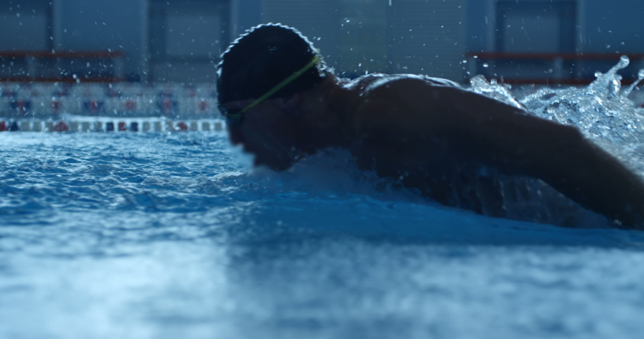 A professional swimmer raising a lot of splashes is swimming in butterfly style along his path in the pool. Slow mo, slo mo, slow motion, high speed camera