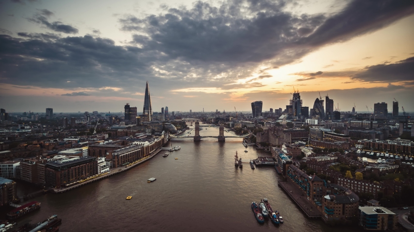 Establishing Aerial View shot of London Tower Bridge City Skyline Thames River Shard Great Britain United Kingdom slow track in drone helicopter during amazing sunset in May