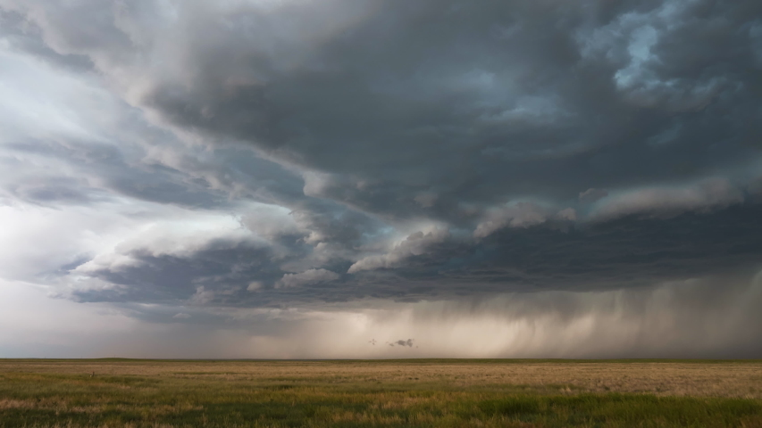 Clouds moving in time lapse bringing dramatic storm as it moves over the plains.