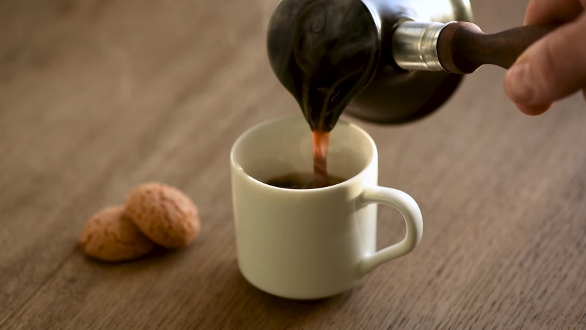 Pouring black coffee in cup. Espresso coffee using turkish coffee maker | Shutterstock HD Video #1041579253