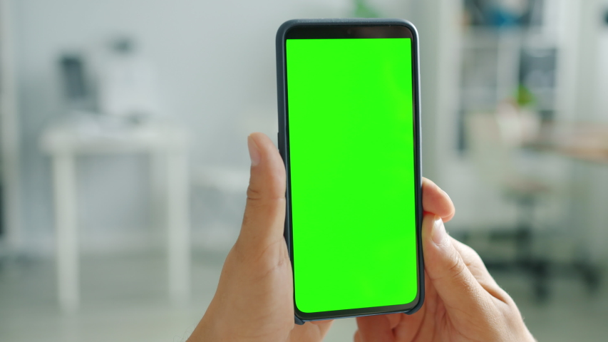 Contemporary smartphone with green screen copy space mock-up in male hand on blurred domestic background. Digital devices and online content concept. | Shutterstock HD Video #1041584278