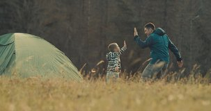 Happy traveler father and son playing, bonding near tent camp around mountain under sun light enjoying the leisure and freedom. 4K slow motion video