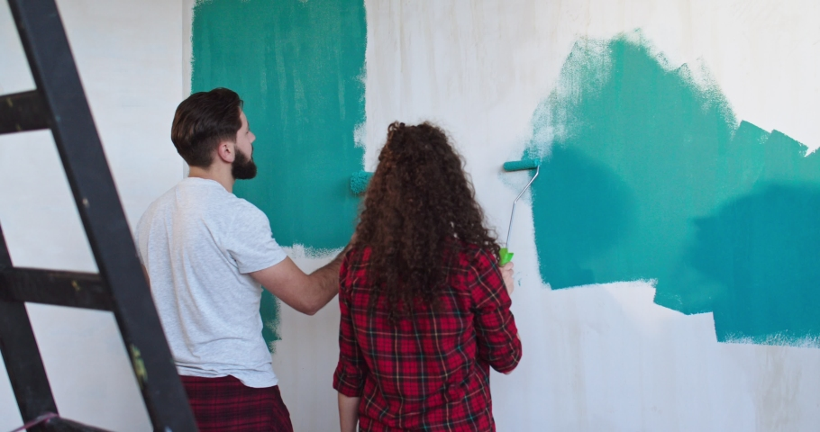 Caucasian happy young just-married couple painting walls in blue color with a wall roller brush while renovating their house. Rear. Stay home | Shutterstock HD Video #1041592261