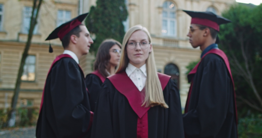 Camera zooming in on the young beautiful blonde master graduated girl in glasses and academic gown standing in front of the camera and looking straight to the camera. Outdoors. Portrait shot. | Shutterstock HD Video #1041592345
