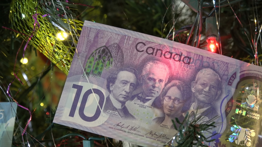 TORONTO CANADA - NOV 22 2019: Canadian dollar bill on a Christmas tree with blinking Christmas lights in the background
