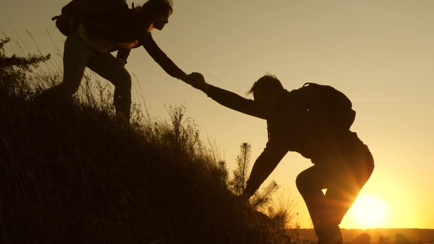 adventure and travel concept. Woman traveler holds out his hand to a man traveler climbing to the top of hill. Tourists climb the mountain at sunset, holding hands. teamwork of business people #1041595402