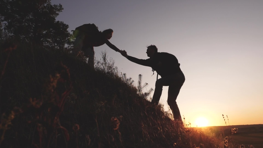 Adventure and travel concept. Woman traveler holds out his hand to a man traveler climbing to the top of hill. Tourists climb the mountain at sunset, holding hands. teamwork of business people | Shutterstock HD Video #1041595408