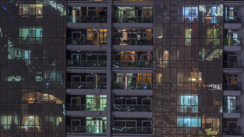 Night view of exterior apartment building timelapse. High rise skyscraper with blinking lights in windows with people moving inside. Zoom in | Shutterstock HD Video #1041596497