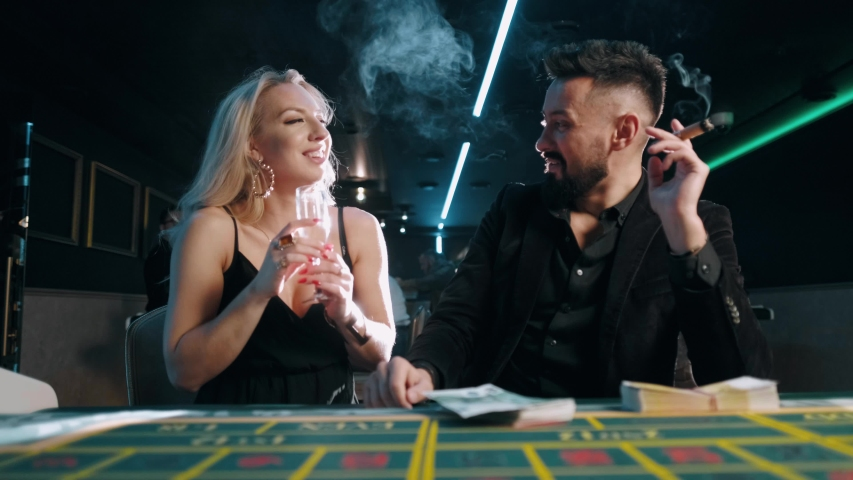 Bearded man with money in a casino. Rich businessman in suit is flirting with a beautiful woman. | Shutterstock HD Video #1041599503