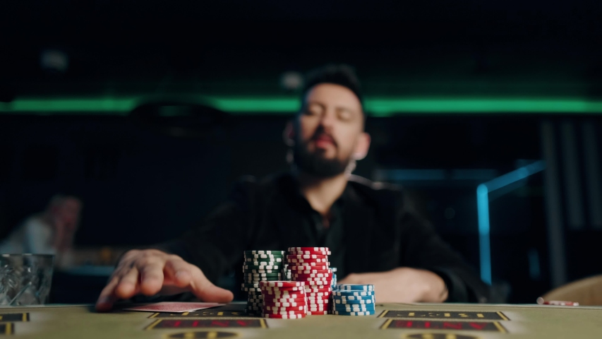 Bearded man is playing poker in casino. Man is throwing his cards on the table | Shutterstock HD Video #1041599566